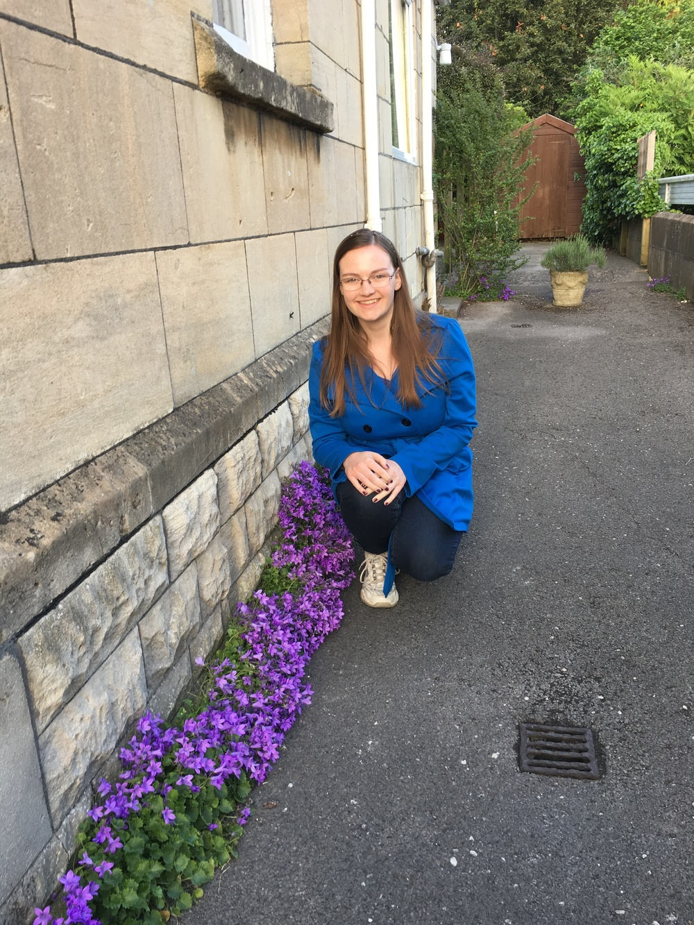 My sister posing with some purple flowers outside of Parkside B&B.
