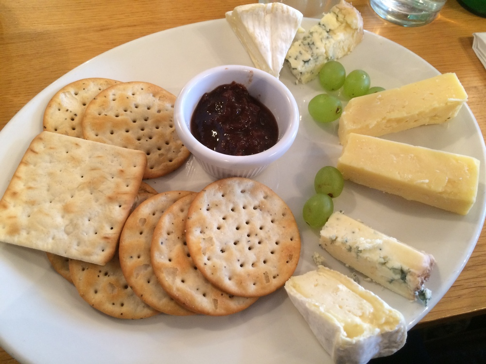 The cheese plate. Cheeses, clockwise from top: brie, blue, white cheddar, blue, and brie. Served with various crackers (left), onion jam (middle) and green grapes. Yes, onion jam sounds weird, but it is amazing and I wish I could find it in the US.