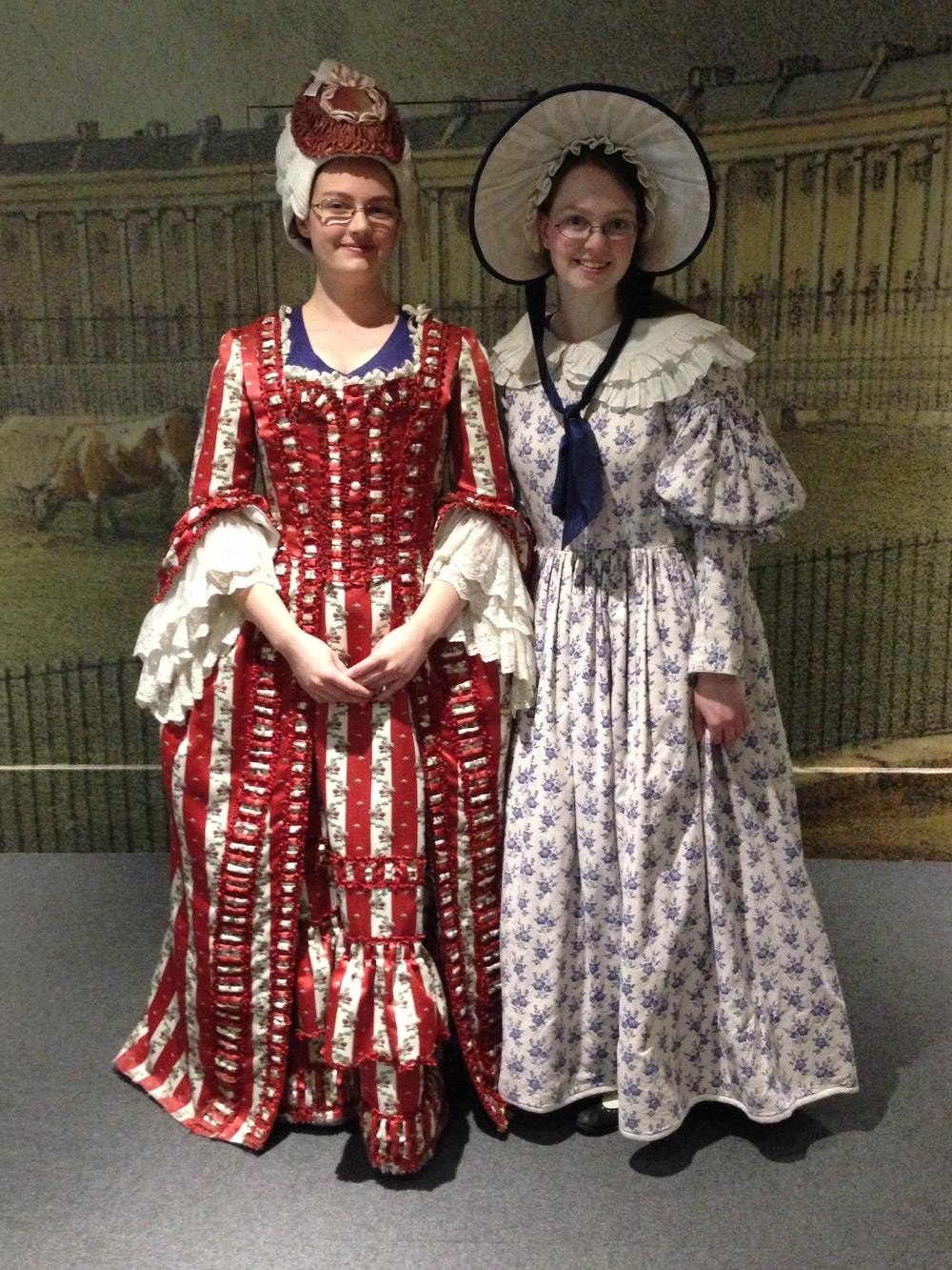 My sister in an 18th-century costume and wig, me in a 19th-century costume and hat.