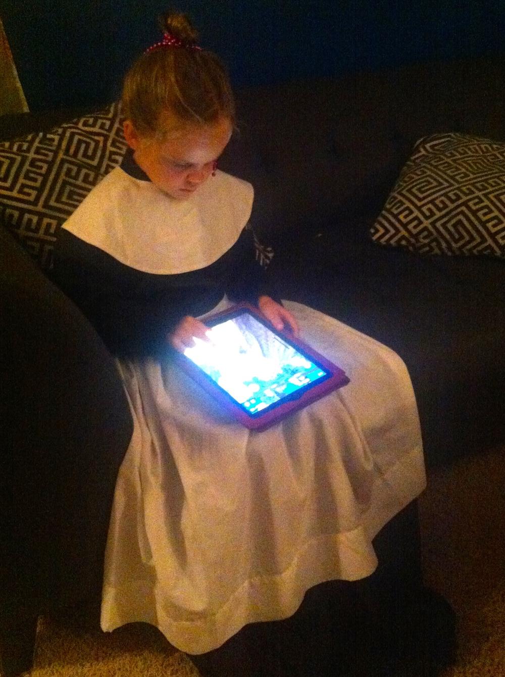 a little pilgrim playing iPad games