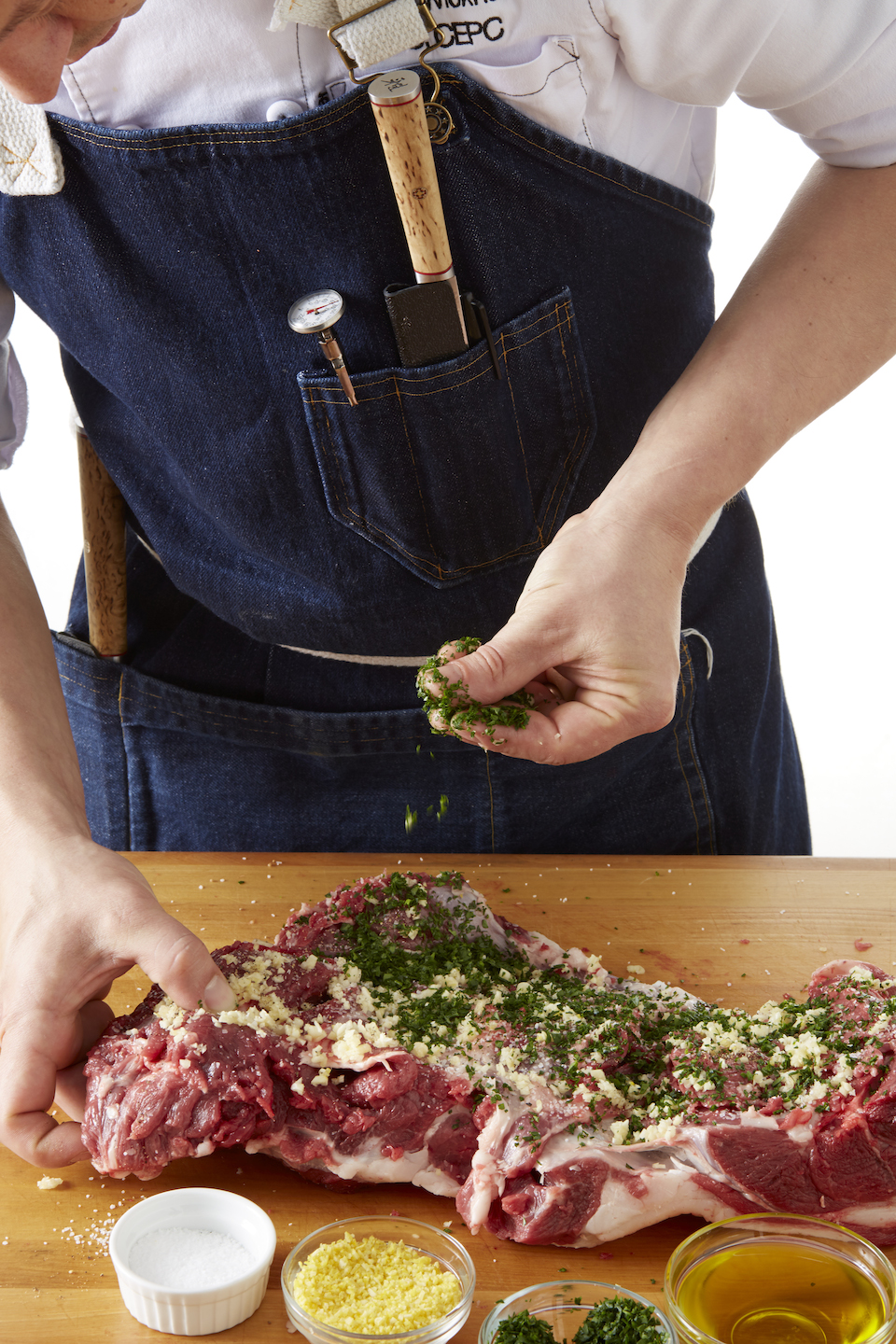 Step Two: Season the lamb with salt and pepper, then spread the lemon-garlic-parsley paste over the seasoned meat.