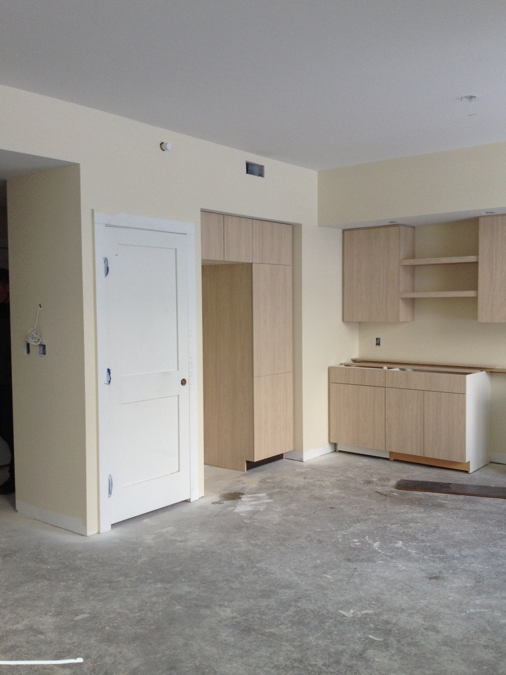 Kitchen cabinets, Refrigerator nook, and pantry in Unit 102.
