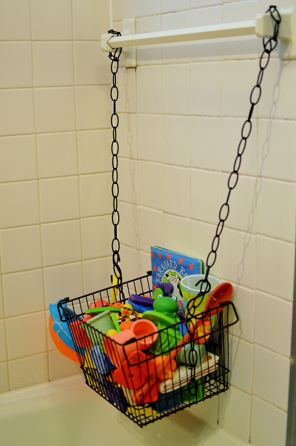 Simple Solution:  Use a basket and chains to create a sturdy, sophisticated bath toy bin.