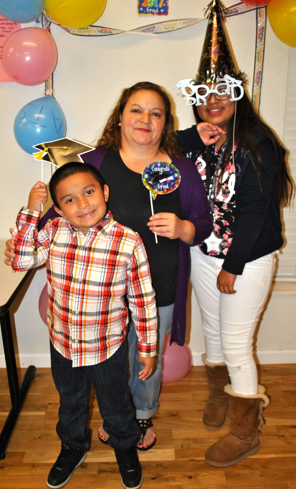 Middle School Graduation - A parent attending BCM's middle school graduation party poses with her children for a photo.