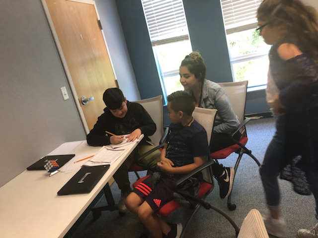 BUSINESS - OUR BUSINESS INTERN AND SCHOLARSHIP RECIPIENT HELPS INSTRUCT STUDENTS IN THE CREATION OF A BUSINESS PROPOSAL.