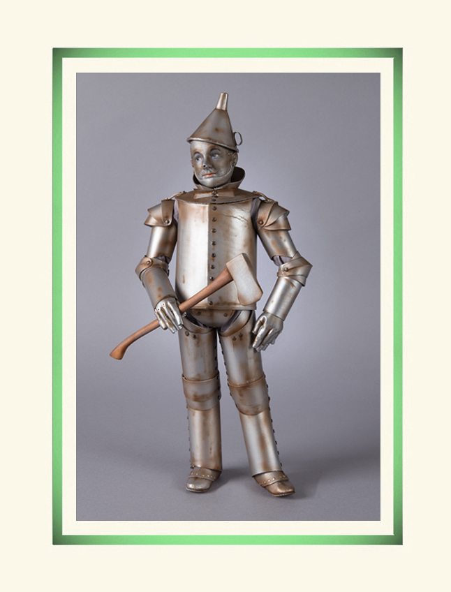 Faithfully based on the beloved character immortalized by Jack Haley in the 1939 film, the Tin Man has been brought to life by for the first time in the medium of molded felt. The R. John Wright Tin Man is the most faithfull recreation of this character ever produced. Standing 18 inches tall, he is an all-felt doll fully jointed at the neck, shoulders, elbows, hips and knees with the RJW ball & socket jointing system with an internal wood mechanism. Beneath his costume, the Tin Man has a realistic molded felt torso and limbs. Under his gloves, his amazing sculptural felt hands have individually sewn fingers! The character face has been finely sculpted in a true likeness and skillfully molded out of felt with hand painted features and a hand-applied metallic complexion. Extensively researched for the utmost authenticity, the Tin Man's iconic costume has been precisely recreated in one-quarter scale. The suit is made just as the original was using several layers of buckram, a stiff fabric coated with glue. The buckram parts are bonded to silver paper and joined together with metal rivets to allow movement. The costume is accessorized with detailed gloves, a funnel hat (also crafted out of buckram), and a wooden replica of the original Tin Man's axe. No detail been spared to bring this beloved film character vividly to life as never before.