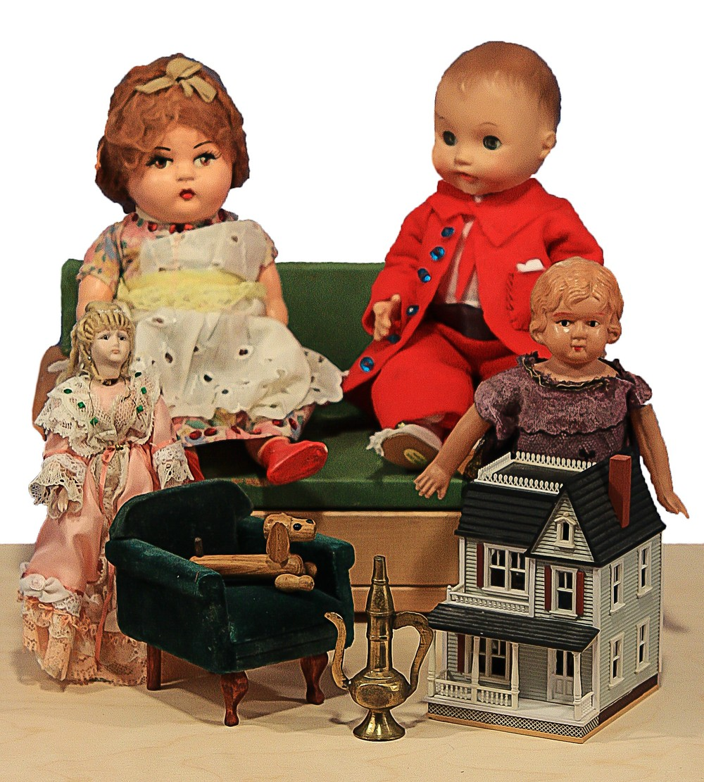 My own Plantagenet family, inspired by The Dolls' House; L to R, Top: Birdie, here as a vintage composition doll from Mexico, dressed By my Grandmother. I did the pinafore. To her right, Mr. P, a vintage Effanbee Baby doll I dressed in a red flannel suit. Bottom: L, Marchpane, an all bisque Jumeau replica; I dressed her and did her wig of mohair. Darner, a jointed wood dog here sitting on a vintage velvet chair from Boston, vintage brass coffee pot from India, vintage 1/144 scale doll house; it opens and is furnished. Far right, a celluloid antique doll, similar to the original Birdie. My doll house, built by my Dad, is called Plantagenet House.