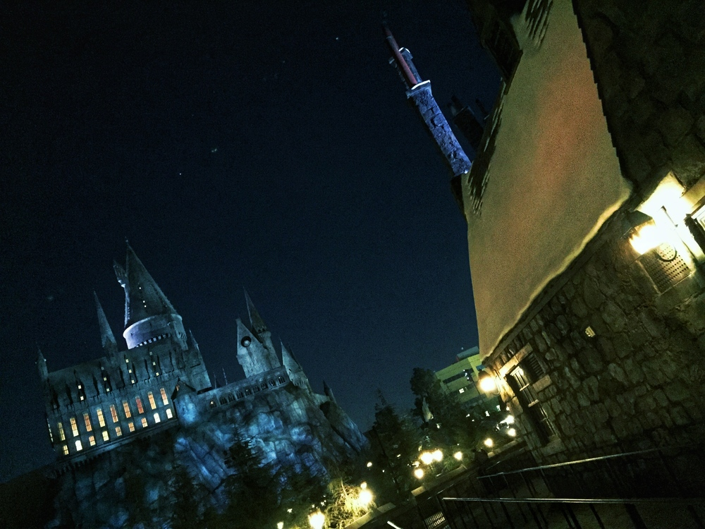 Night time view of Hogwarts castle from the Three Broomsticks dining patio.
