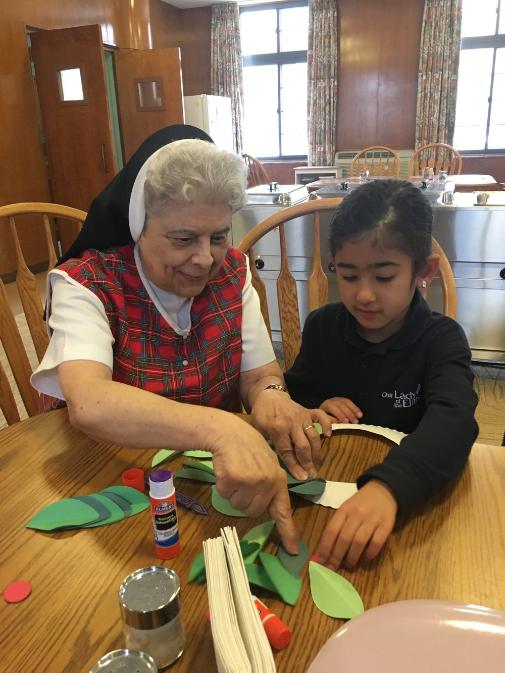 Crafting with the Dominican Sisters of Peace.Kindergartener Gabby Takla works on a holiday wreath with Sister Philomena.