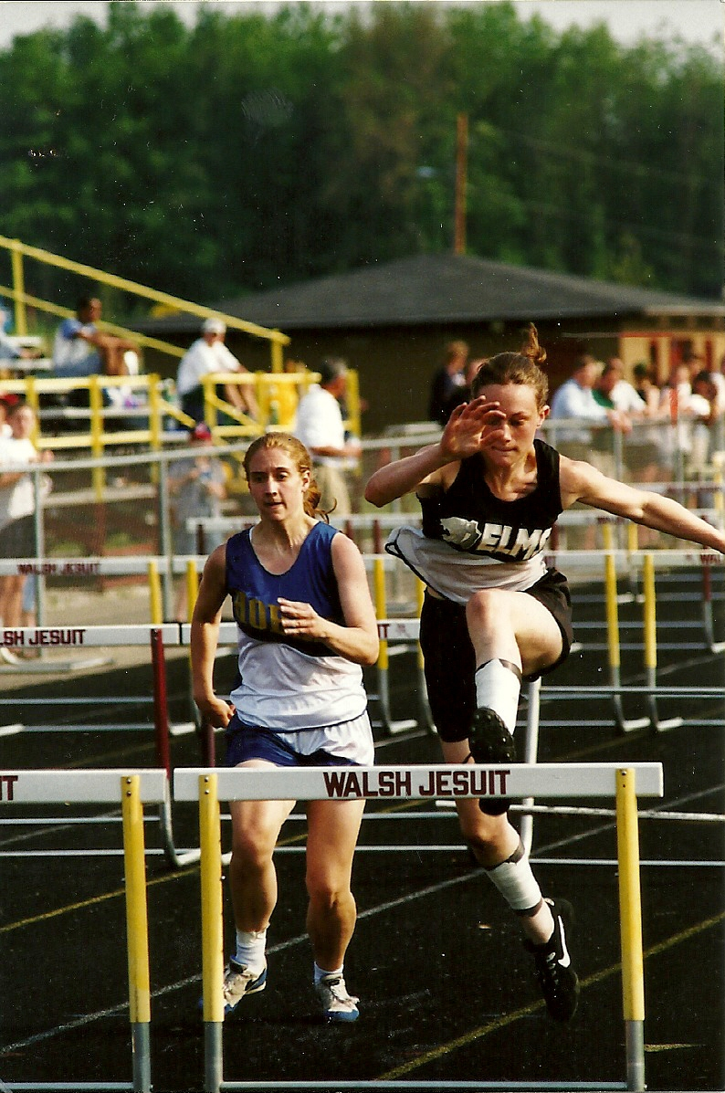 Mary Laske Bell  (right) competes in the hurdles at a meet during her high school track career.