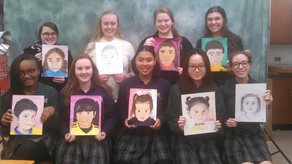 Students display their works of art for the Memory Project.