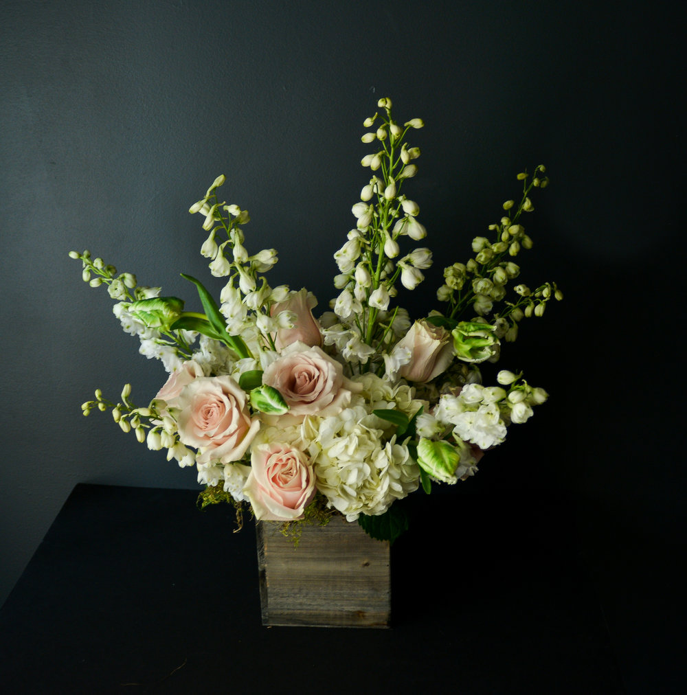 $150 Arrangement   Reaches up and out, a stunning centerpiece for attention, packed with florals and greens. Special occasion florals can be used in these arrangements, while still keeping fullness in play.