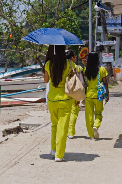 Three Asian Massage Girls dressed in yellow uniforms blue umbrella walking at beach promenade, Sabang Puerto Galera Philippines