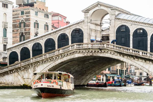 Venice, Italy. A vaporetto, a Venetian waterbus, under the Rialto Bridge on the Grand Canal.