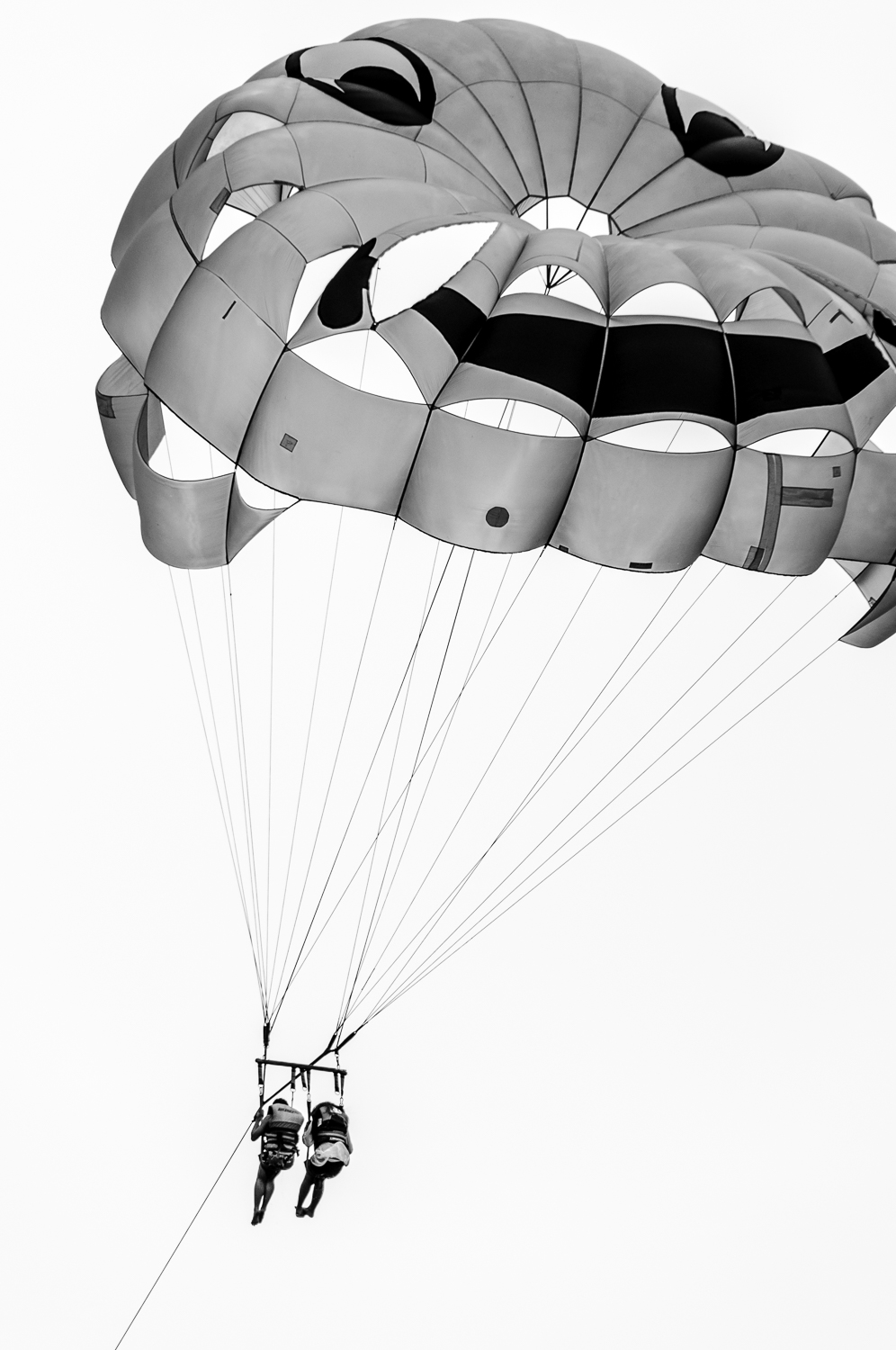 2 Women Paragliding With Smiley Face - In Black And White