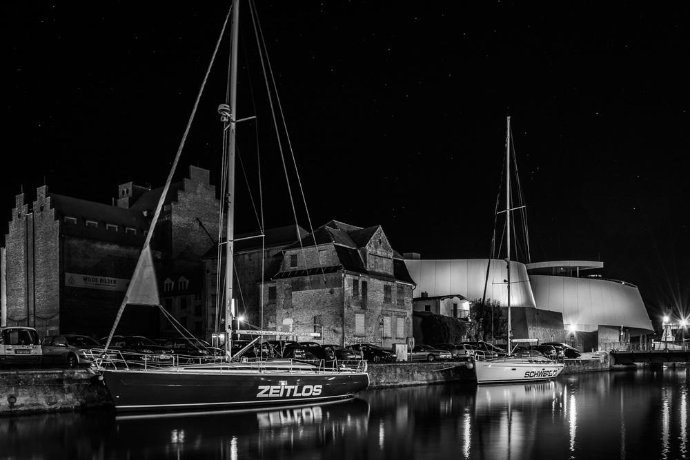 Segelyachten auf dem Fährkanal Stralsund vor dem Ozeaneum bei Nacht