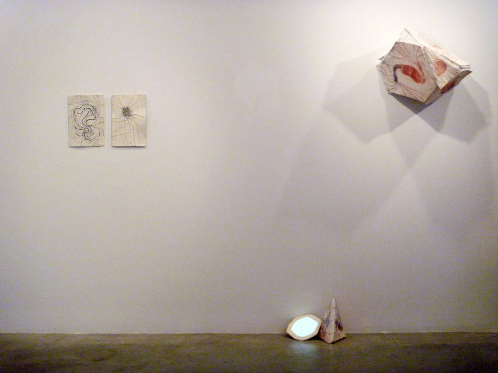"""Installation view:  Path Maps #1, 10-D Cube  (looped video animation projected onto a clay tablet) and  Tetrahedron (Truncated) with Pyramid  .        10-D Cube  is an animation projected onto a clay slab. As the animation moves forward, its lines connect to the pre-existing drawing, and then loops by going in reverse.  10-D Cube  is taking the original structure of a Tesseract (a four dimensional cube) and following the same method, continues to add on """"dimensions"""" in time. The result is the build-up of information becoming so dense that the viewer loses track of what they are looking at."""