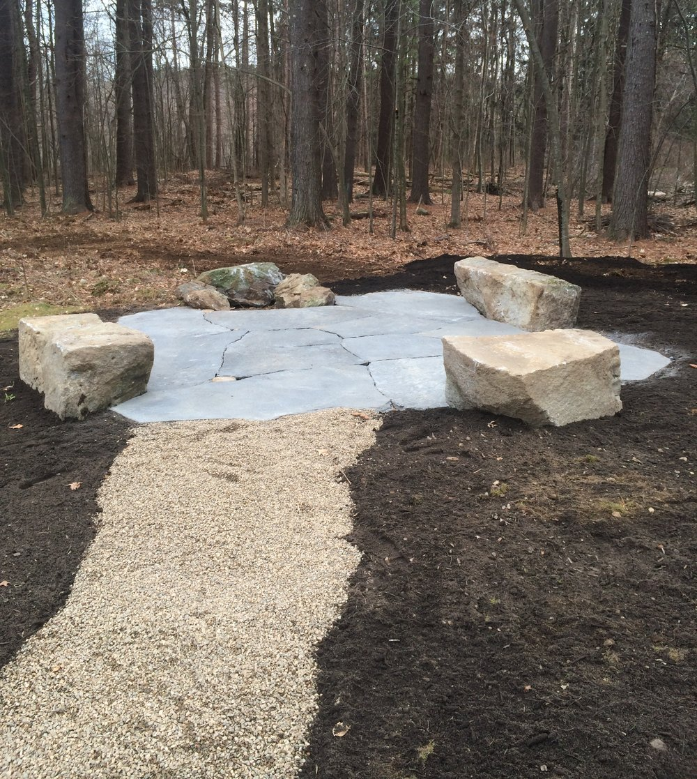 goshen stone patio with granite benches, firepit, and washed stone walkway