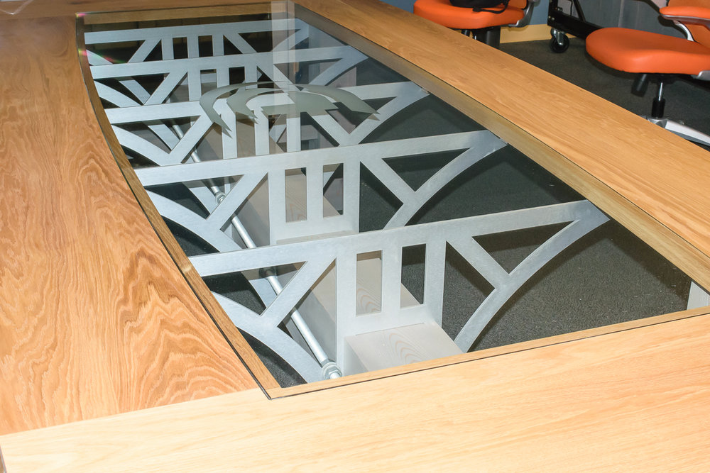 Conference Table: Created for Racine-based Design Department, this conference table features a machine-cut cedar top, oak legs, sanded aluminum, and a custom engraved center glass cutout. See more.