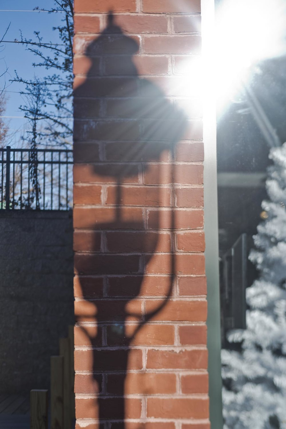 Desaturated red brick with strong shadow of a lamp.
