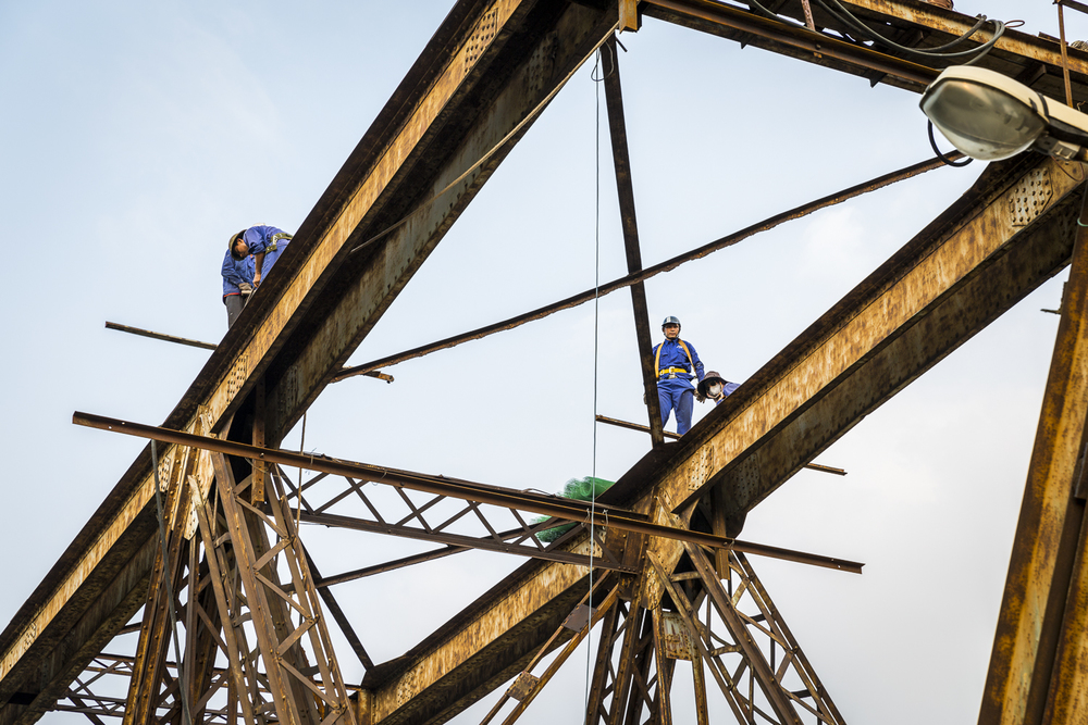 Working without a net and 50 feet up with zero safety gear workmen carry out repairs to the top of the cantilever bridge.