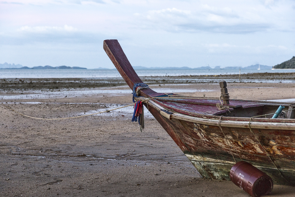 Washed up. A long tail boat languishes on the beach at low tide. Phuket Island. Thailand.