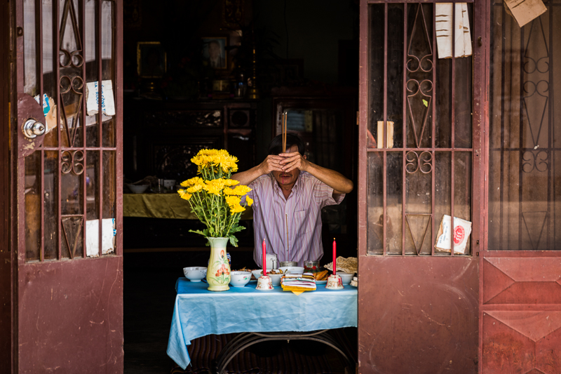 On the eve of Tet a man prayer for his departed relatives at an ancestral alter temporarily set up at the front of his house, facing the street for good luck.