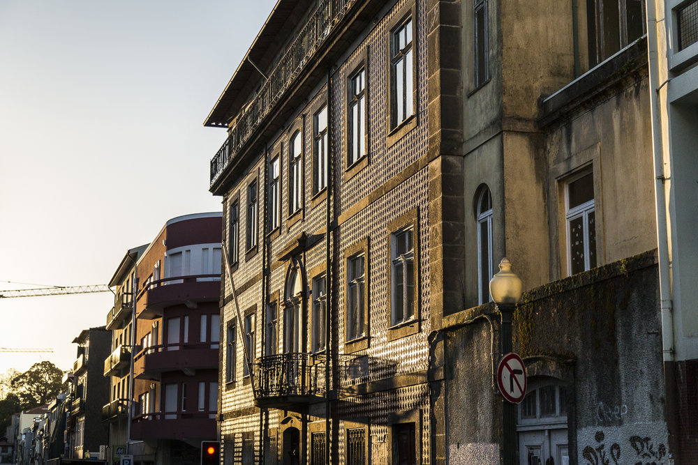A building decorated with Azulejo tiles glows in the light of a Porto sunrise.