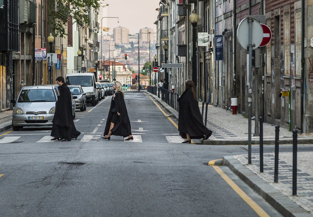 Abbey Road meets Harry Potter. University students in their traditional black capes cross the street.