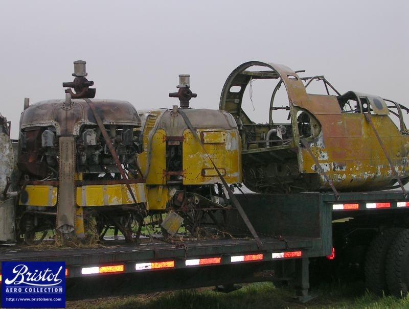 The two Bristol Mercury engines and the forward fuselage are loaded on the first truck