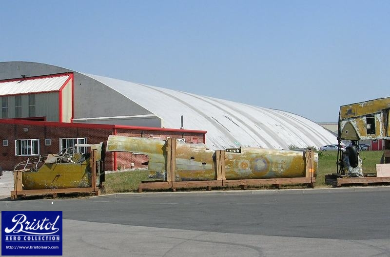 The front and rear fuselage sections of Bolingbroke 9048 lined up outside the Airbus factory. The aircraft was painted yellow during its career as a trainer, but traces of its operational livery can be seen underneath.