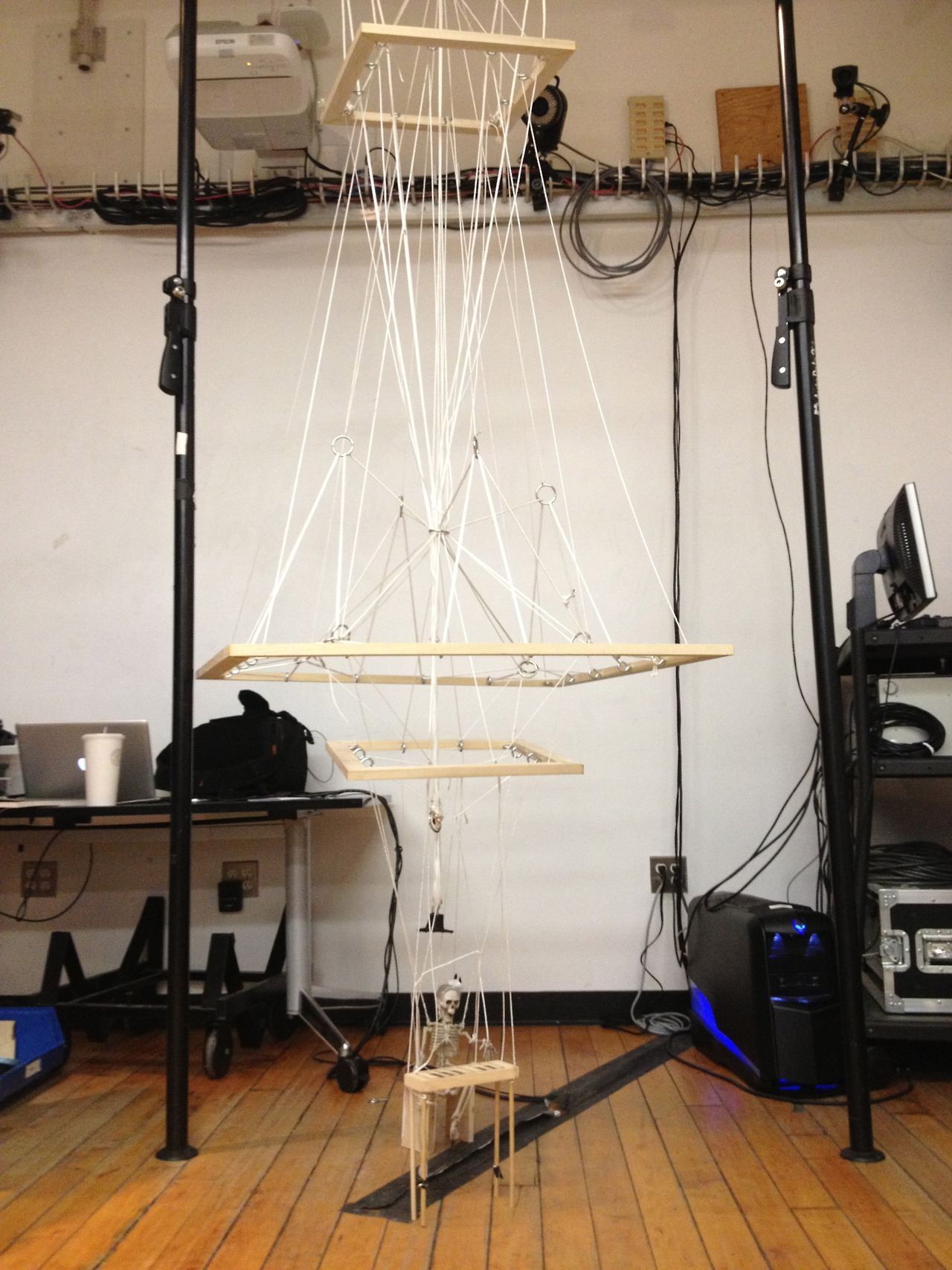 Rube Goldberg rope sculpture: when the frames move, the skeleton is lowered onto his tiny piano