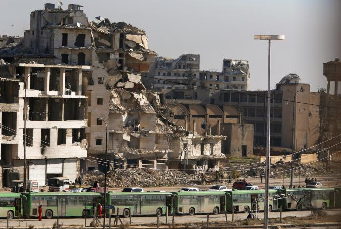 A convoy of green busses is seen evacuating Aleppo civilians; photo from  Reuters