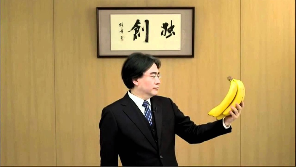 Iwata looking at bananas in a funny skit promoting a Donkey Kong game