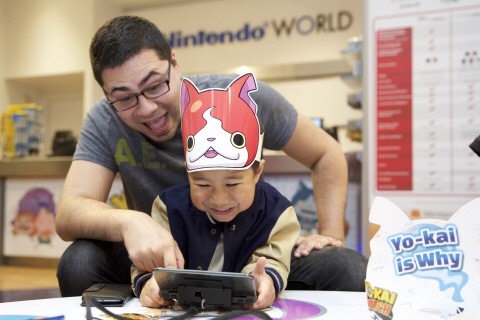 For Photo # 1  In this photo provided by Nintendo of America, David C. and son Dylan C., 4 years old, from Forest Hills, New York, play the YO-KAI WATCH game for the Nintendo 3DS family of systems at the Nintendo World launch event in New York on Nov. 7, 2015.