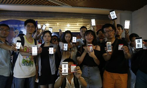 "A   group of filmgoers show their phone screens with a message that reads, ""refund our tickets,"" in protest against a Jason Bourne 3D screening at a Beijing cinema on Thursday. Photo: Li Hao/GT"
