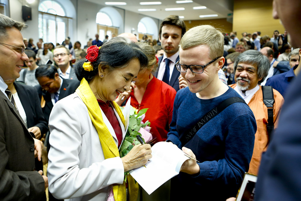 Aung San Suu Kyi signs an autograph at University of Warsaw in 2013. Image source: flickr/undpeuropeandcis