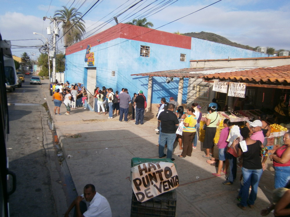 Venezuelans are shown waiting in line to buy food. Source: Wikipedia