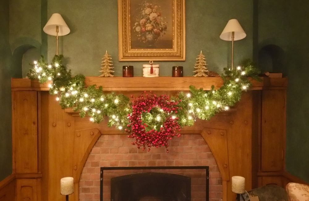 One of many beautiful and festive mantels in this gorgeous home. This is faux greenery with a beautiful berry wreath. It really pops off of the wall.