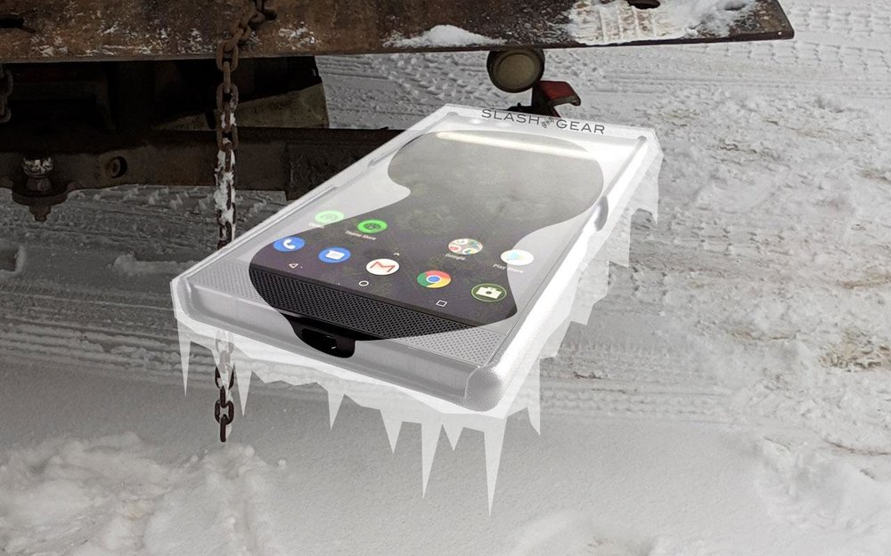 The subject of the article here was smartphone functionality in deep cold conditions. The Razer Phone here was photographed for a review, and was photographed on a white background to allow the end product to be used on any background. The ice is just two layers of semitransparent white clipped out and pasted over the phone. The background is a photo I'd taken earlier in the week of a tow truck that'd picked up my dysfunctional car.