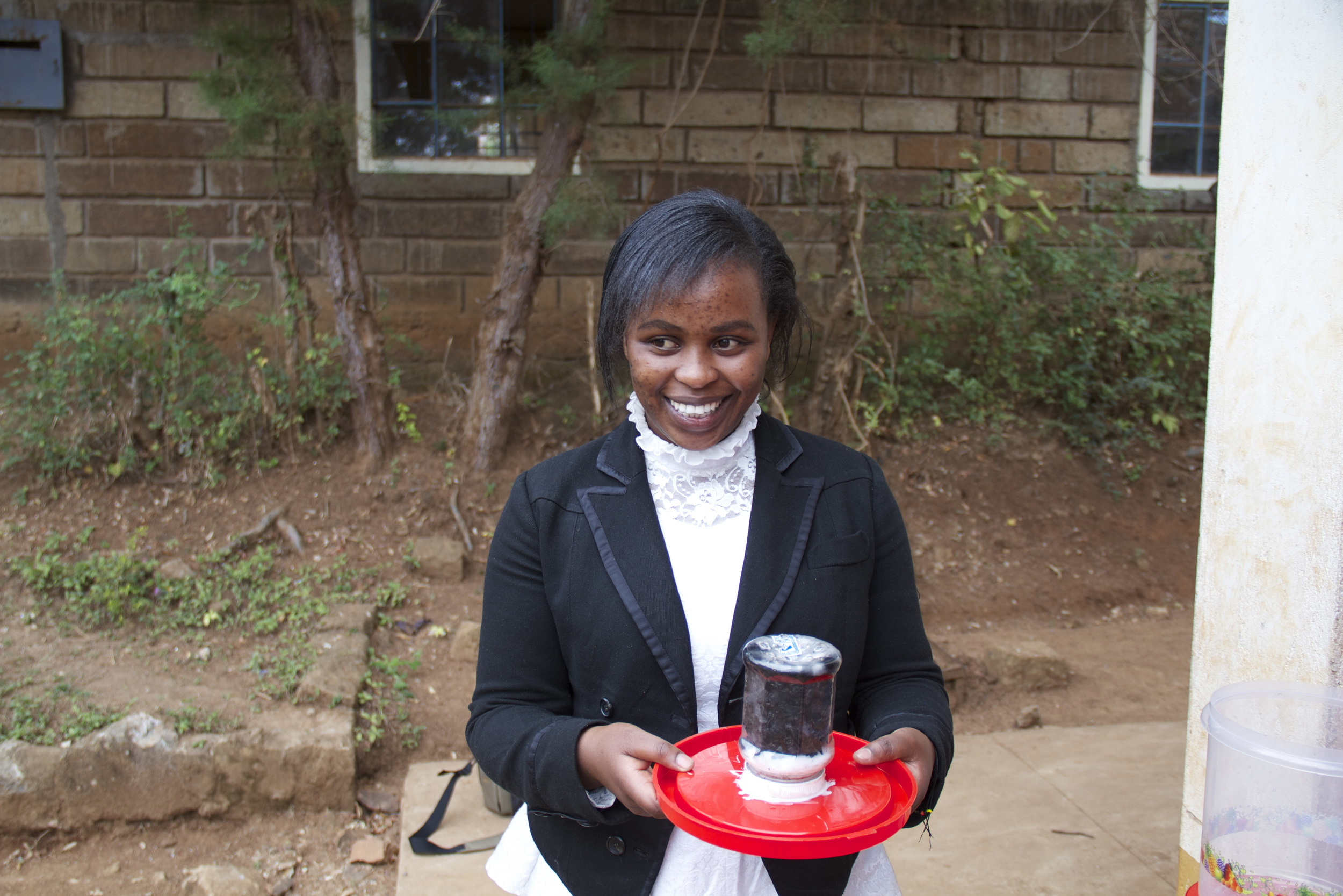 Beth showcasing the charcoal water filter on a project site visit in 2014