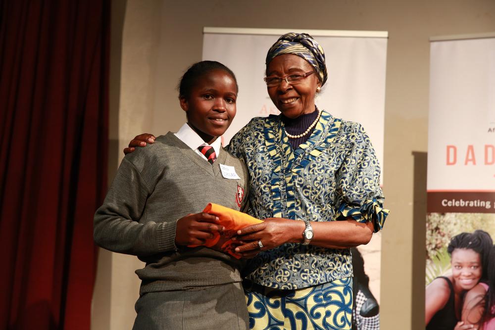 Dr. Eddah Gachukia awarding Akili Dada Scholar during 'Women of Excellence Awards' session