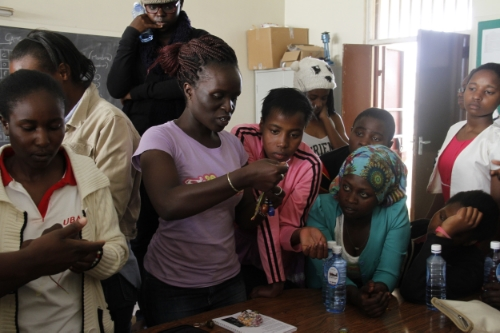 Yvonne Akoth (centre) teaches girls and young women from Akili Dada and her program how to make jewelery from beads at her training centre in Nairobi during the recent Akili Dada East Africa Girls Summit