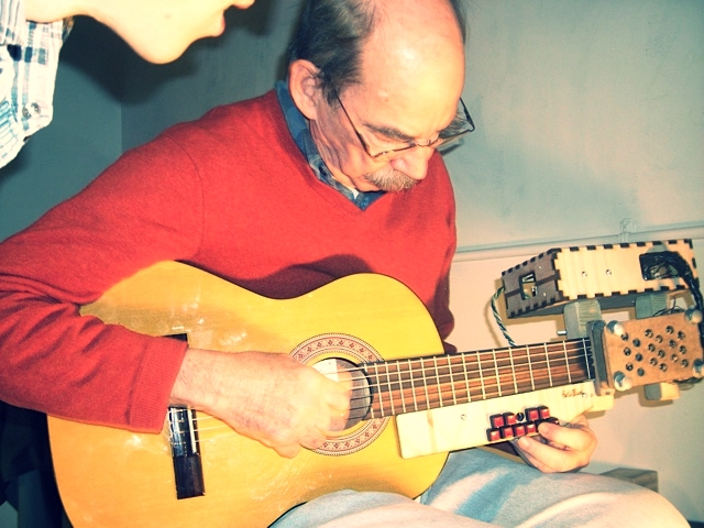 Photo of a man playing a modified guitar with buttons on the fretboard while another man looks on.