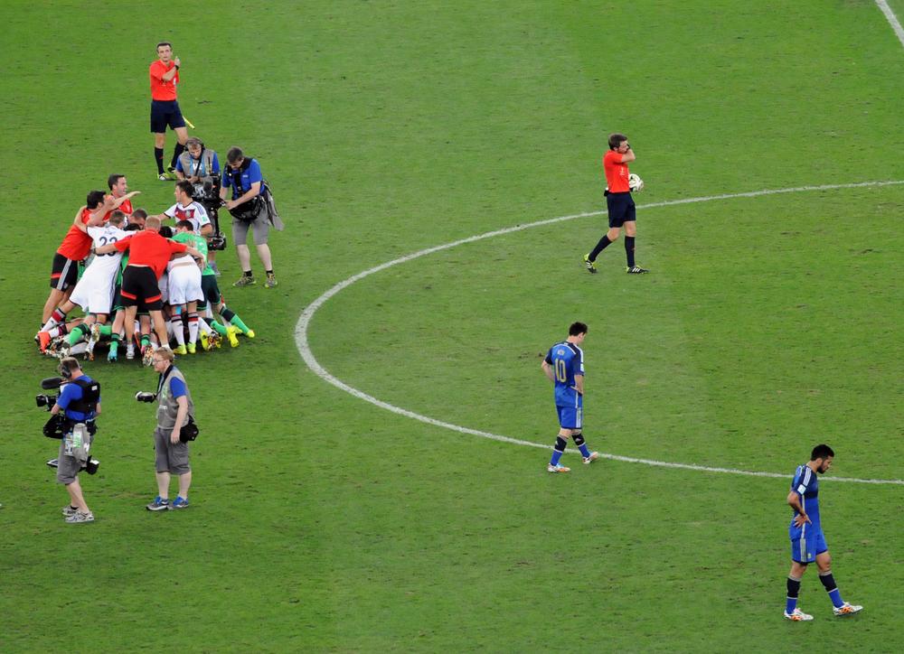 El árbitro italiano Nicola Rizzoli ya pitó el final. Alemania se consagra Campeón del Mundo por cuarta vez en su historia al vencer a Argentina por 1-0 en el Estadio Maracanã de Río de Janeiro el 13 de julio de 2014. Los jugadores alemanes celebran mientras los argentinos Messi y Garay sufren la derrota. Foto: Eduardo Biscayart.