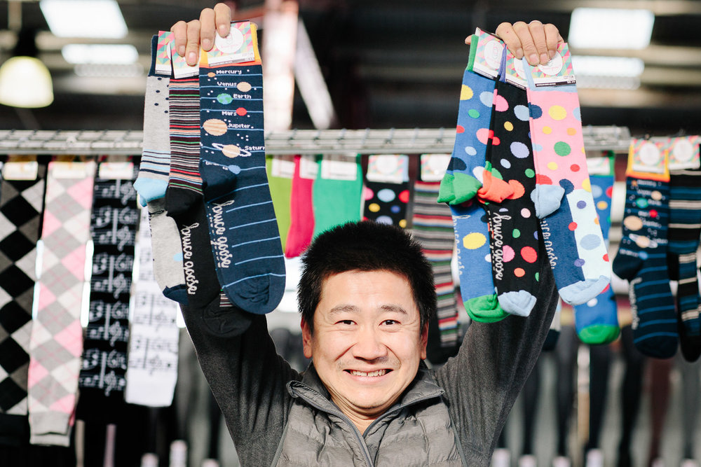 Bruce Pham holding up a selection from his  Bruce Goose  range of high-quality Australian-made merino wool socks. His family have been selling socks and hosiery at the market since 1987. Photograph by Emma Byrnes.