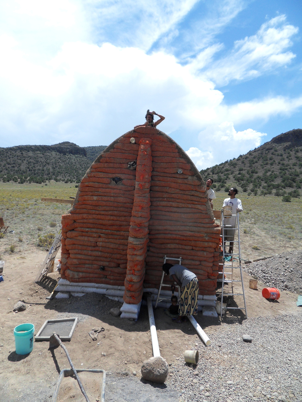 Natural Building with Earthen Hand & Regenerative Lifestyle.  Papillon hammering the last bamboo stake in this hyperadobe wall of a Nubian vault construction in La Garita, Colorado.