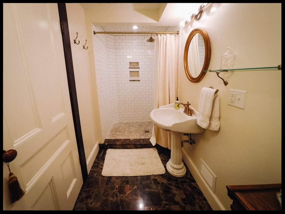 Empire room with tile shower and pedestal sink