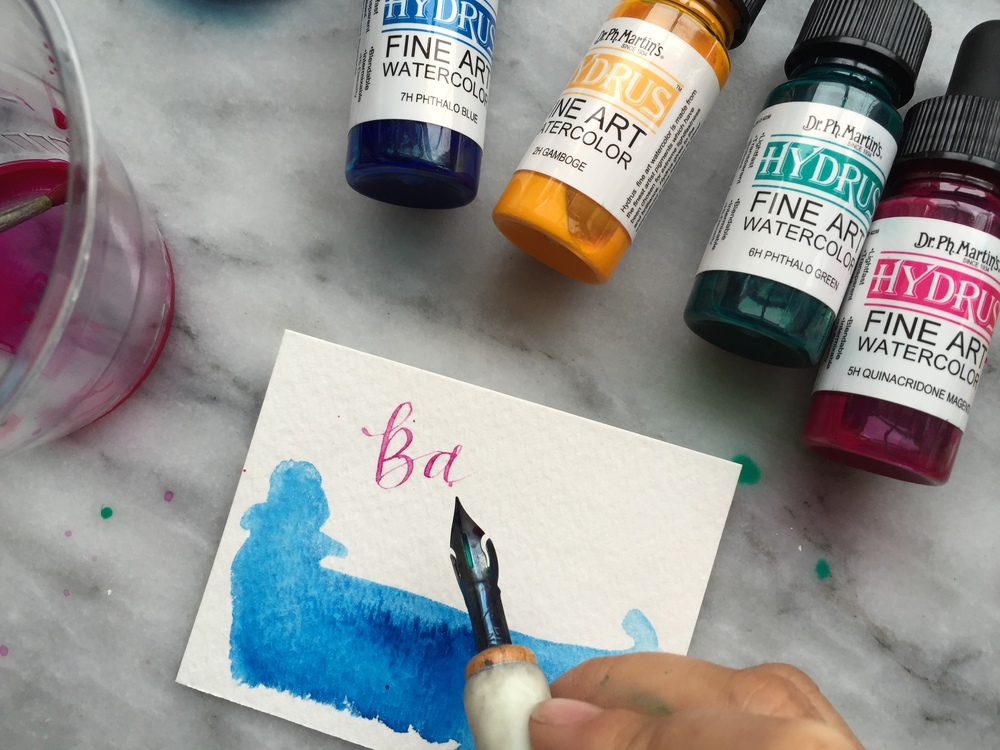 I would then paint a different color on the nib. (Lean the nib and nib holder upright.) I would just fill just a little bit of watercolor, just enough to write a few letters.