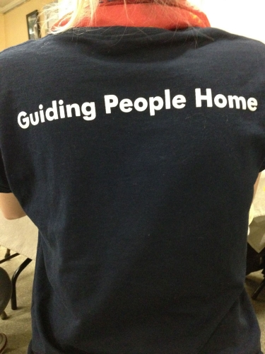 A staff member wears a T-shirt with the Miriam's Kitchen motto on the back.